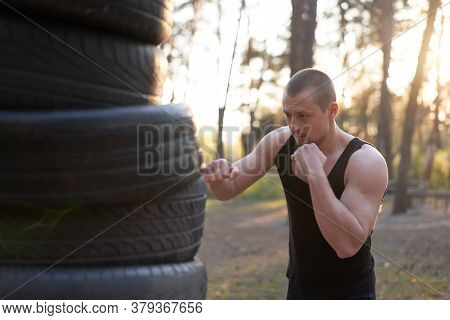 Man Fighter Training Boxing Outdoor Tire Diy Handmade Gym In Forest Fitness Workout. Young Adult Tra