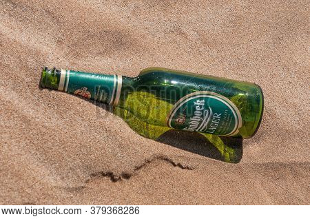 Walvis Bay, Namibia - June 8, 2011: An Empty Beer Bottle On Dune 7 At Walvis Bay On The Atlantic Oce