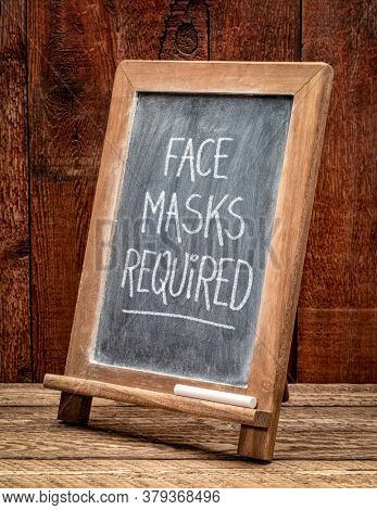 face masks required - white chalk handwriting on a blackboard, coronavirus covid-19 pandemic concept