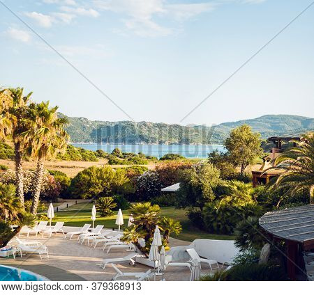 Mediterranean Landscape. Sunbeds with Umbrellas. Luxury Panoramic View on Mediterranean Sea. Sardinia. Italy.