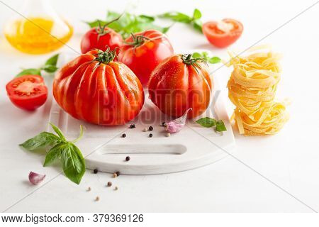 Assorted tomatoes with basil, garlic, spice and raw pasta for italian cuisine. Healthy food concept on white background