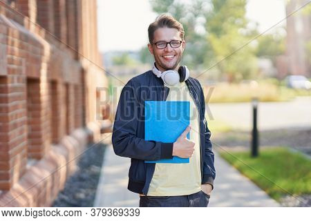 Male student in the campus studying outdoors