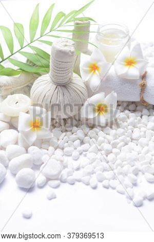 Spa setting with bottles of essential oil , , frangipani , herbal ball, ,candle cream,green palm on pile of white stones