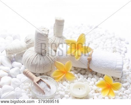 Spa setting with pile of white stones and yellow frangipani flowers ,candle with, herbal ,ball,rolled towel