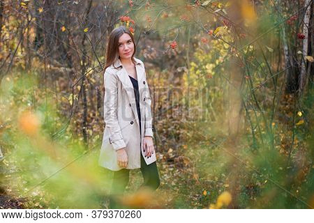 Beautiful Slender Girl In A Raincoat In The Autumn Forest At Sunset. Warm Light. Yellow And Red Foli