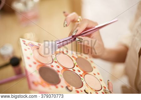 A Young Beautiful Asian Woman In A Beige Lace Dressing Gown Put On Morning Makeup And Uses Eye Shado