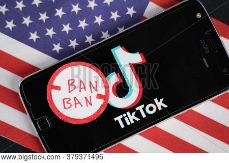 Maski, India - 4 August, 2020 : Tiktok Logo On Phone And Ban Stamp With America Flag Background.