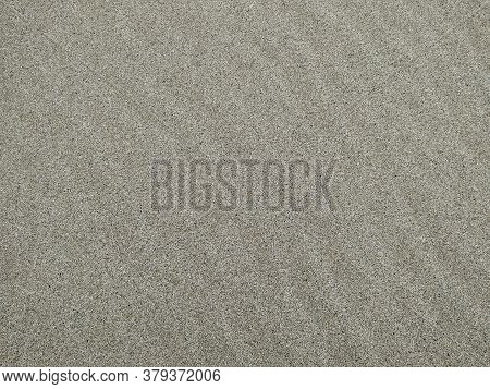 Sand On The Beach Grange Background. Grey Grainy Texture. Summer Background With Space For Text.