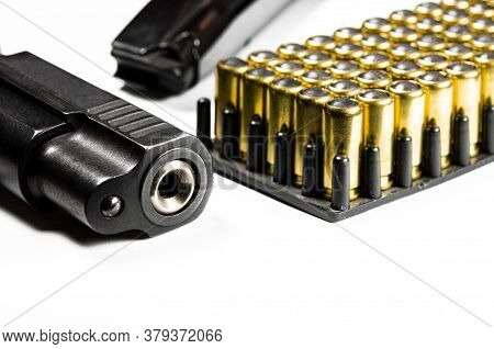 A Black Pistol With Bullets For Shooting Lie On A White Background.