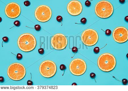 Orange Slices And Sweet Cherries On Blue Background. Food Wallpaper, Summer, Vgetarian Concept