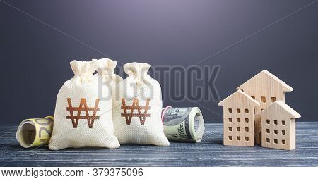 South Korean Won Money Bags And Residential Buildings Figures. Investments In Real Estate. Mortgage