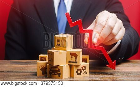 Businessman Holds A Red Down Arrow Over The Boxes. Business Industrial Production Drop Rate. Shortag
