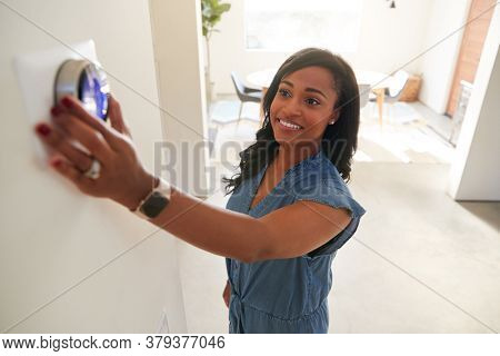 Woman Adjusting Digital Central Heating Thermostat At Home