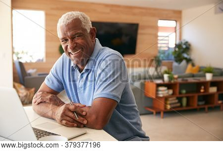Portrait Of Senior African American Man Using Laptop To Check Finances At Home