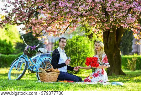 Couple In Love Picnic Date. Spring Weekend. Romantic Picnic With Wine. Flowers Symbol Of Romance And
