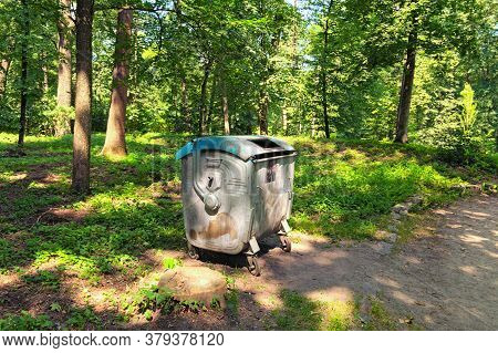 Garbage Dumpster. Four Wheeled Trash Can. One Metal Container For Garbage In The City Park. Ecology
