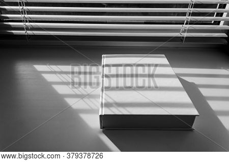 A White Book With Sharp Shadows Lies On A White Window Sill