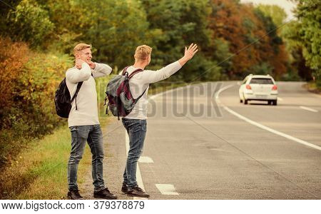 Feeling Of Being Free. Twins Walking Along Road. Stop Car With Thumb Up Gesture. Hitchhiking And Sto