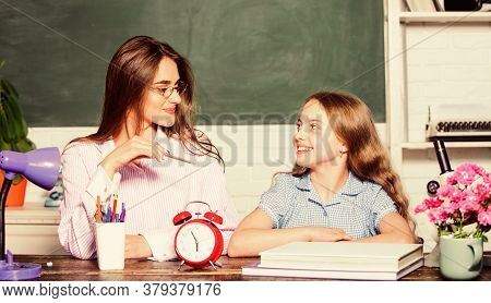 Doing Homework With Mom. Little Girl And Woman Sit At Desk. School Education. Studying Together. Hel