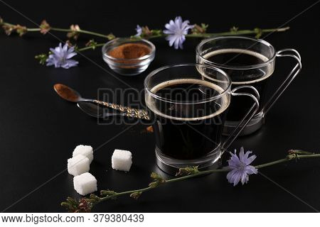 Chicory Beverage In Two Glass Cups, With Concentrate And Flowers On Black Background. Healthy Herbal