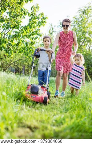 Young Boy Mowing Grass With Lawn Mower, His Mother And Little Sister Encouraging Him