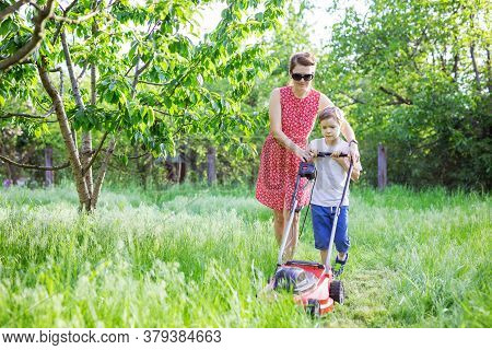 Mother And Son Mowing Grass With Lawnmower In Garden