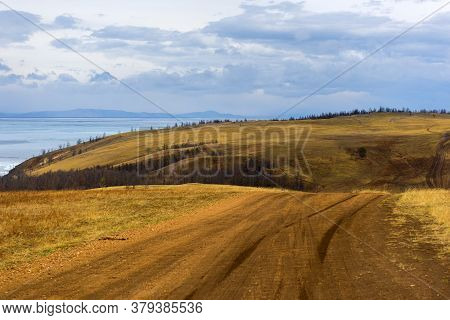 Track Winding Back Roads In The Mountains. Dirt Road On Olkhon Island In Lake Baikal. For Guide To R