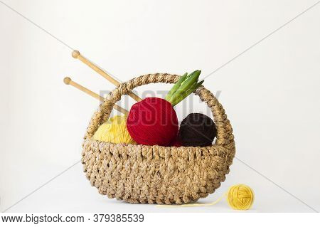 Bright Red, Yellow, Brown Balls Of Yarn, One With Green Leaves Of Hyacinth In Small Basket With Knit