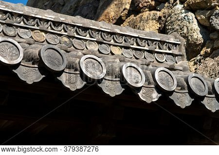 Himeji, Japan, 06/11/19. Old Carved Royal Family Crests And Decorations Adorning Roof In Himeji Cast