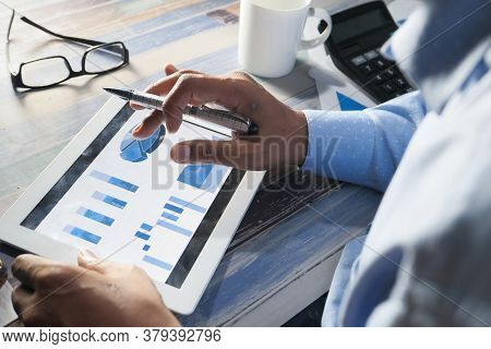 Mans Hand Working On Digital Tablet At Office Desk, Using Self Created Chart