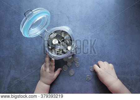 Top View Of Baby Child Saving Coins In A Jar,