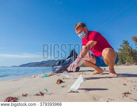 Activist Volunteer Man In Medical Face Mask Pick Up Garbage That Pollute Beach Sand Near Sea. Proble