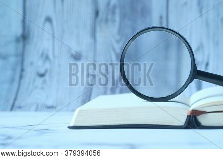 Open Book And Magnifying Glass On Table.