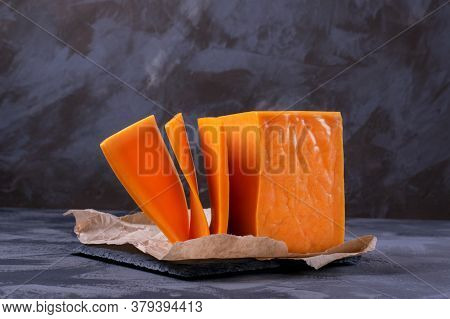 Red Cheddar Cheese Block Cut Into Slices Against The Grey Background