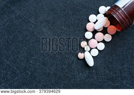 Top View Of White Pills Spilling On Black Background