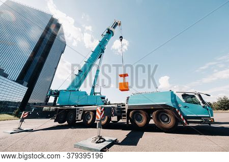 A Large Blue Truck Crane Stands Ready For Operation On A Site Near A Large Modern Building. The Larg