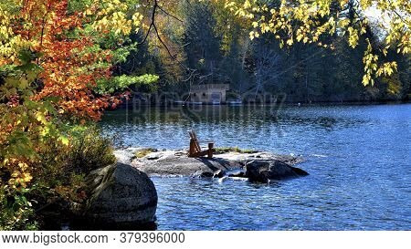 Two Adirondack Chairs Sitting On A Rocky Shore Facing A Calm Lake With Autumn Leaf Colour