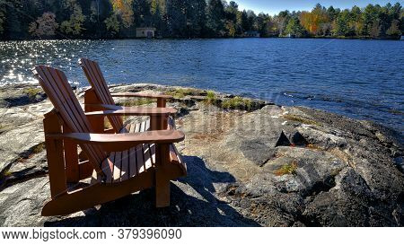Two Adirondack Chairs Sitting On A Rocky Shore Facing A Calm Lake With Trees In The Background