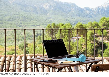 Still Life View Of Open Laptop Computer On A Wooden Patio Patio Table With Mobile Headphones And Not