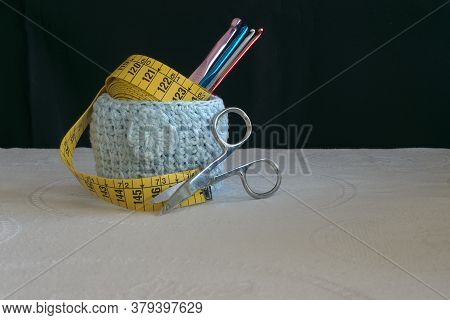 Hooks And Meter In A Crochet Cup With Black Background.
