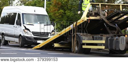 Wrecked Minibus Stands Next To Tow Truck. Broken And Wrecked Car Transportation Services Concept