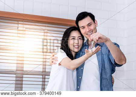 Portrait Images Of Asian Couple, The Husband Is Delivering The House Key To His Attractive Wife As A