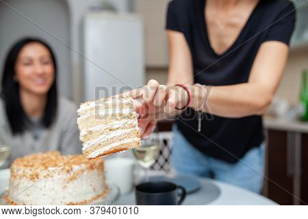Friends Meeting With Wine And Cake In The Modern Style Kitchen. Women Smile And Joke. Two Girls Drin