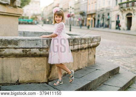 Adorable Little Blond Girl In Beautiful Pink Dress Posing To Camera At Old Fountain Of Ancient Europ