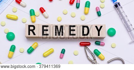 Medical Concept. Remedy Word On Wooden Blocks, Multicolored Pills, Medical Syringe, Scissors.