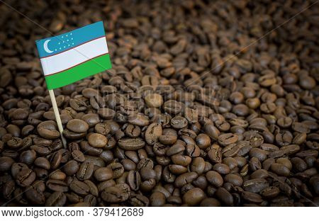 Uzbekistan Flag Sticking In Roasted Coffee Beans. The Concept Of Export And Import Of Coffee