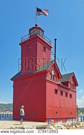Caucasian Man Standing By Big Red Lighthouse In Holland Michigan Harbor