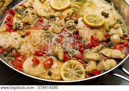 Italian Chicken Piccata With Artichoke Hearts And Capers Cooking In Large Pan
