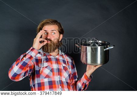 Bearded Male Chef Cook Or Baker Holds Saucepan Shows Sign Ok. Cooking Food Concept. Cooking Pot In C