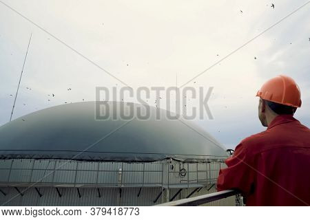 Novosibirsk, Russia - June 20, 2019: Biogas Station. Biological Gas Plant. A Man In A Helmet Looks A